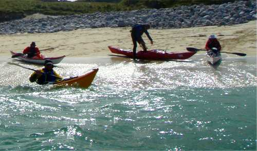 Sea kayakers launching from beach