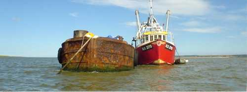 Anchored barge and fishing vessel